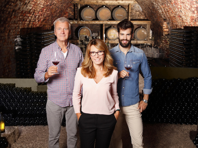 Portrait of multigenerational winery owner family standing at wine cellar. Senior winemaker and young sommelier standing at background and holding in hands a glass of red wine while middle age businesswoman looking at camera and smilig. Small business.