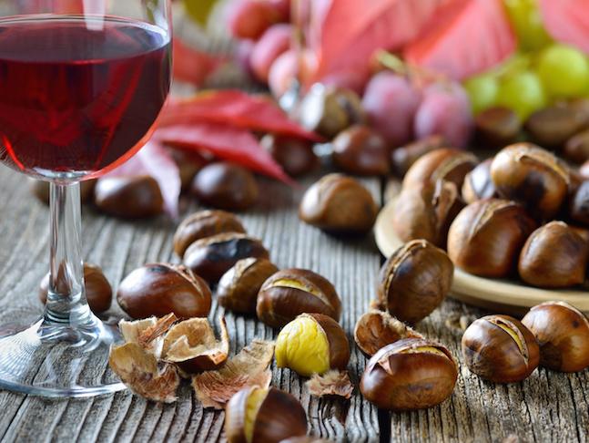 Gerstete Maroni mit neuem Rotwein, weie und rote Weintrauben im Hintergrund