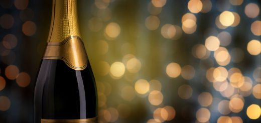 drink, alcohol, advertisement and holidays concept - close up of bottle of champagne with blank golden label over lights background