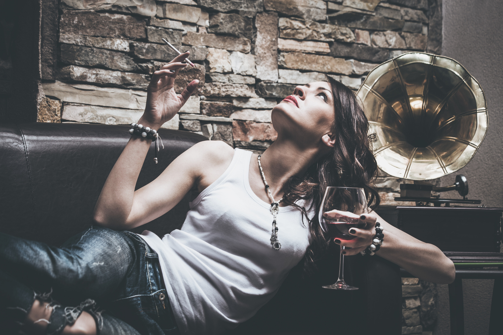 woman with glass of red wine and cigarette, wearing blue jeans and white t-shirt, lie on leather couch, behin her is old gramophone, indoor shot